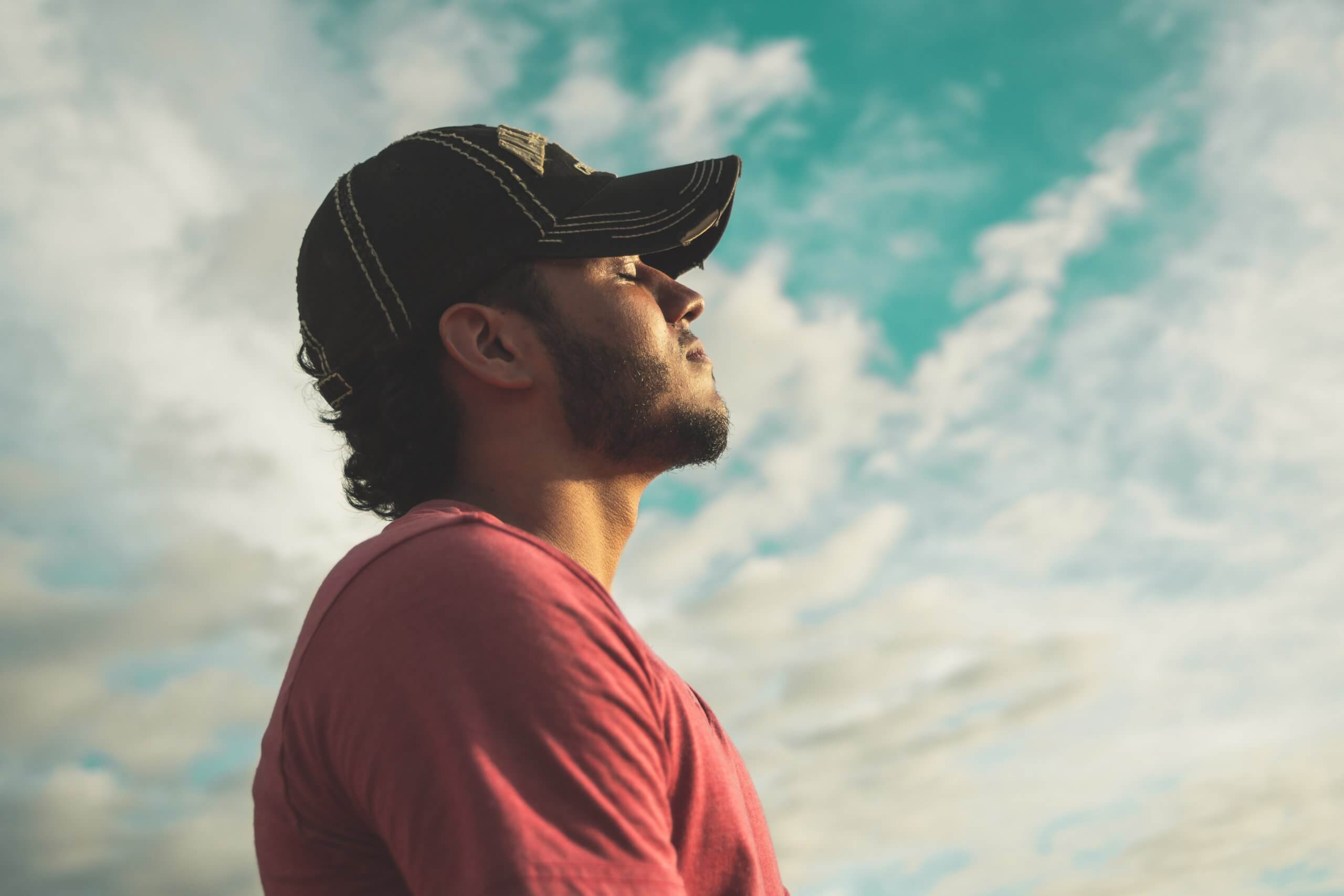 man-wearing-black-cap-with-eyes-closed-under-cloudy-sky-810775